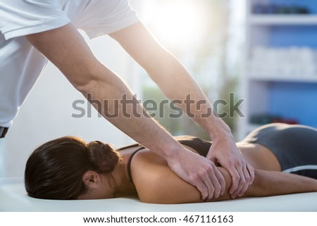 Woman receiving arm massage from physiotherapist in clinic