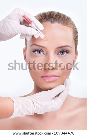 Woman receiving botox injection in the eyebrow zone - stock photo