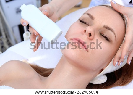Woman receiving cleansing therapy with a professional ultrasonic equipment in cosmetology office - stock photo