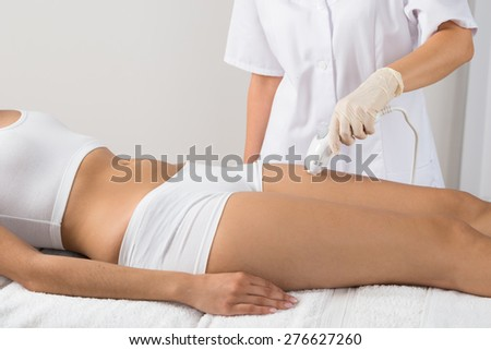 Woman Receiving Epilation Laser Treatment On Thigh At Beauty Clinic - stock photo