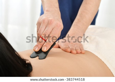 Woman receiving gua sha acupuncture treatment on back - stock photo