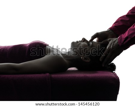 woman receiving head massage in silhouette studio on white background - stock photo