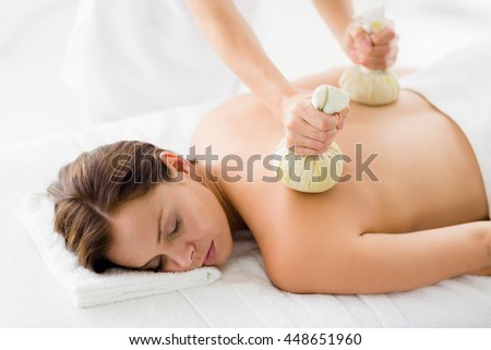 Woman receiving herbal compress massage from masseur at spa