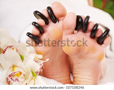 Woman receiving hot stone massage on feet.