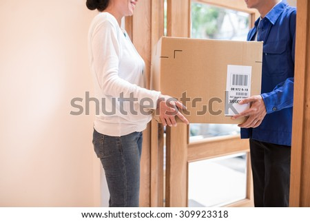 Woman receiving large parcel - stock photo