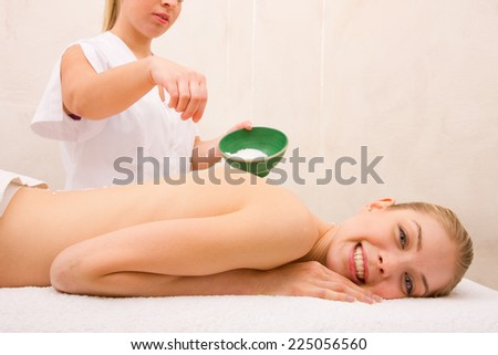 Woman receiving massage with salt crystals spa - stock photo