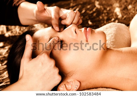 woman receiving professional face massage in spa salon