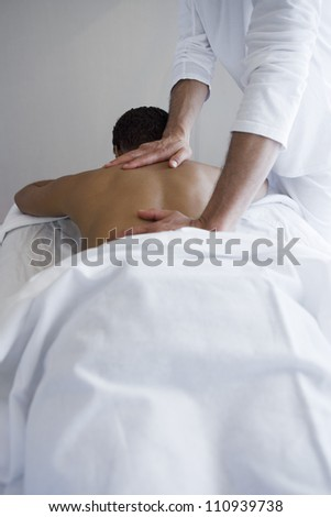 Woman receiving shoulder massage at spa - stock photo