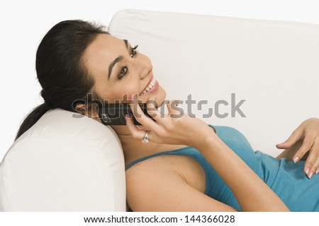 Woman reclining on a couch and talking on a mobile phone