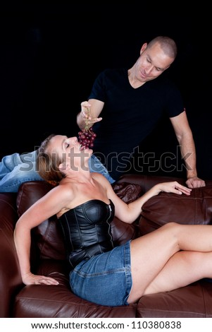 Woman reclining on a couch while her man sits above her, feeding her grapes by dangling them for her to bite - stock photo