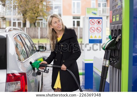 Woman refilling car with fuel - stock photo