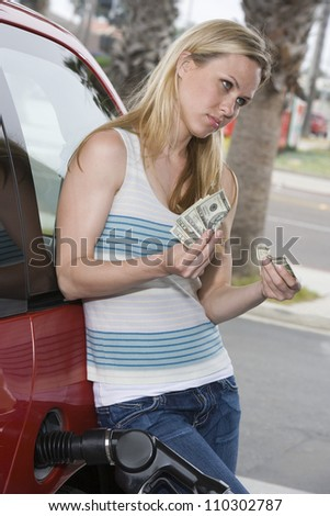 Woman refueling car while counting  money at fuel station