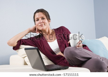 Woman relaxed on couch with laptop computer and coffee cup