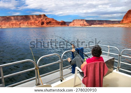 Woman relaxes and enjoys the fantastic views of sandstone cliffs and blue skies.  She is on a houseboat on Lake Powell in Arizona.  She fishes holding the rod with her toes. - stock photo