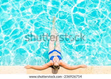 woman relaxes at the edge of the pool - stock photo