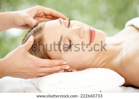 Woman relaxing at a spa having a facial treatment lying back with her eyes closed in enjoyment and a serene expression in a beauty and wellness concept