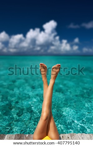 Woman relaxing at beach jetty - stock photo
