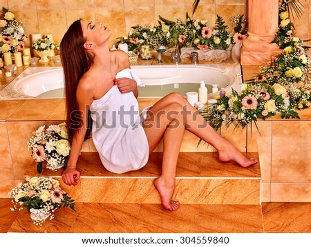 Woman relaxing at flower water. Spa and sauna - stock photo