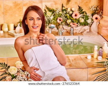 Woman relaxing at flower water spa. Girl sitting near bath. - stock photo