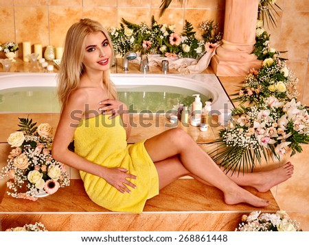 Woman relaxing at flower water spa.Yellow towel. - stock photo