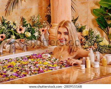 Woman relaxing at flowers water spa. Luxury bath. - stock photo