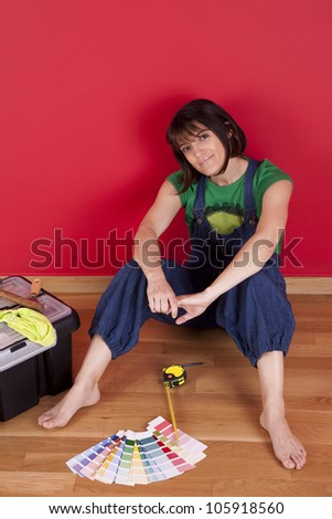 woman relaxing at her house after repairing her red wall - stock photo
