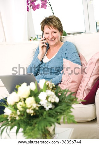 Woman relaxing at home with notebook - stock photo