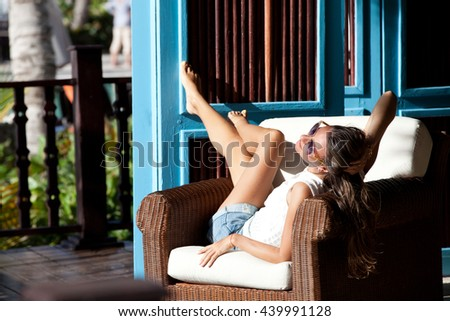 Woman relaxing at resort terrace enjoying luxury lifestyle outdoor day dreaming. Female relaxing on lounge chair. Vacations And Tourism Concept.