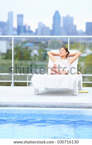 Woman relaxing at rooftop pool in city with skyline in background. Young female model lying down at sun lounger with Montreal skyline in background. - stock photo