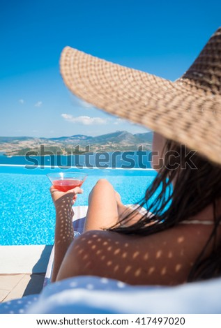 Woman relaxing at the infinity swimming pool looking at view