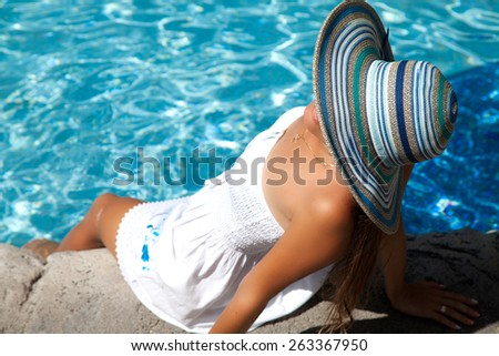Woman relaxing at the luxury poolside. Girl at travel spa resort pool. Summer luxury vacation.  - stock photo