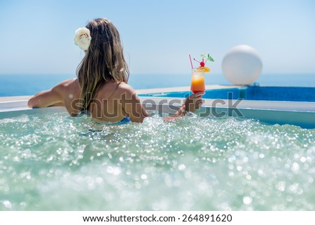 Woman relaxing at the pool with cocktail - stock photo
