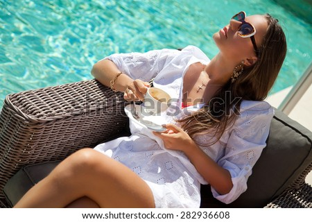 Woman relaxing at the poolside with morning coffee, sunny day, outdoor. Girl at travel spa resort pool. Summer luxury vacation. (focus on woman face) - stock photo