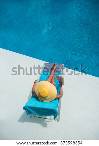 Woman relaxing at the swimming  pool reading a book - stock photo