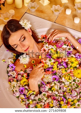 Woman relaxing at water spa. Aqueous surface covers many small flowers. - stock photo