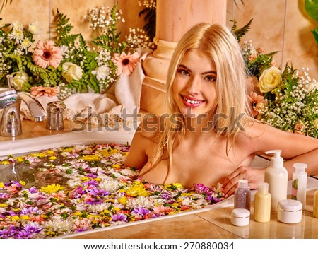 Woman relaxing at water spa. Flower Bath. - stock photo