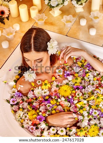 Woman relaxing at water spa. Girl takes a bath with flowers - stock photo