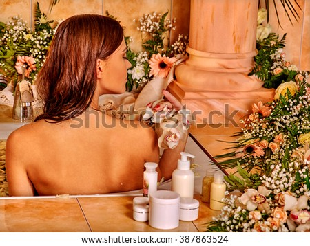 Woman relaxing at water spa. Girl takes a bath with flowers. - stock photo