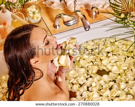 Woman relaxing at water spa. Holding rose petals. - stock photo
