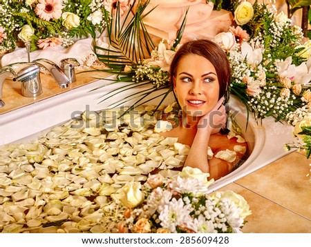 Woman relaxing at water spa in petals.