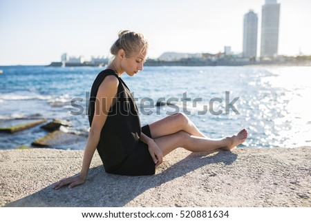 Woman relaxing by the sea during a sunny summer day in Barcelona