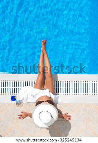 Woman relaxing by the swimming pool in the summertime - stock photo