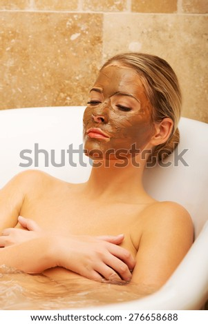 Woman relaxing in a bath with chocolate mask on face. - stock photo