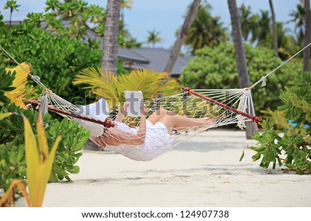 Woman relaxing in a hammock and reading a book on a beach in Maldives - stock photo