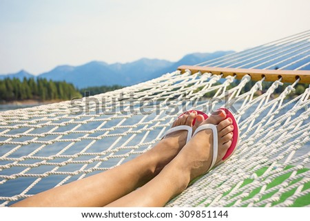 Woman relaxing in a hammock on a beautiful Mountain Lake - stock photo