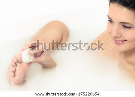Woman relaxing in a hot soapy bath using a pumice stone to exfoliate her feet and remove dead skin cells from the sole in a personal hygiene and skincare concept - stock photo