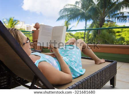 Woman relaxing in a lounge chair while at a tropical resort on vacation - stock photo