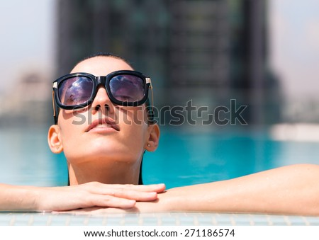 Woman relaxing in a luxurious pool setting.  - stock photo