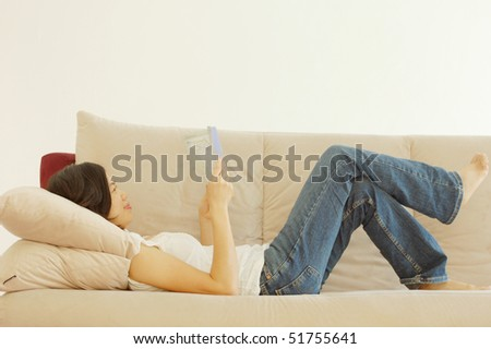 Woman relaxing in a sofa and reading book - stock photo