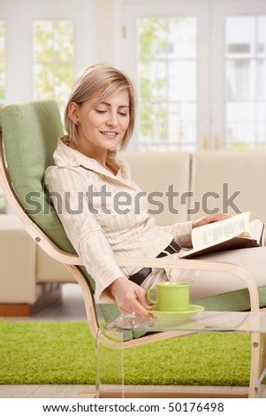 Woman relaxing in armchair at home, reading book, putting coffee on table, smiling.